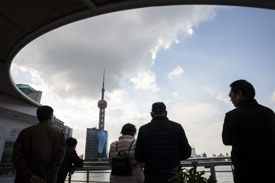People look at the Oriental Pearl Tower while standing on a ferry crossing the Huangpu River in Shanghai, China. Image: Bloomberg