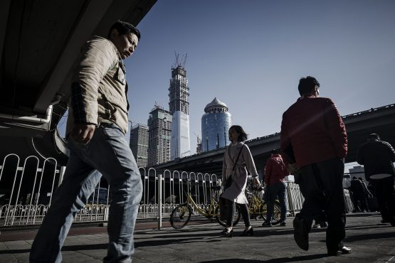 Pedestrians walk along a street as a buildings under construction stand in the background in downtown Beijing, China. Image: Qilai Shen/Bloomberg