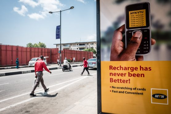 Pedestrians pass by an MTN advertisement at a bus stop in Lagos. Image: Tom Saater/Bloomberg