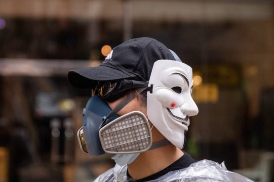 A demonstrator wears a gas mask and an 'anonymous masks', also known as a Guy Fawkes mask, during a protest in Admiralty district of Hong Kong on Sunday, October 6, 2019. Image: Kyle Lam/Bloomberg