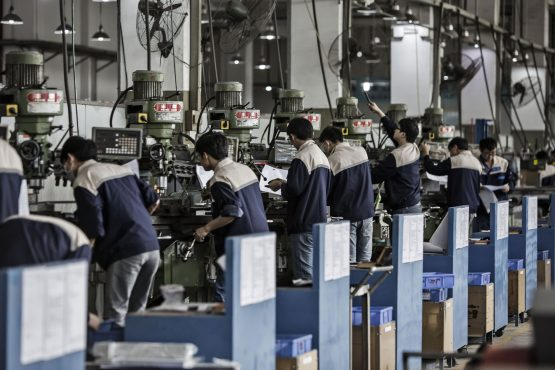 Workers operate machines on the assembly line at a Lyric Robert factory, operated by Guangdong Li Yuanheng Intelligent Automation Co, in Huizhou, Guangdong province. Image: Qilai Shen/Bloomberg