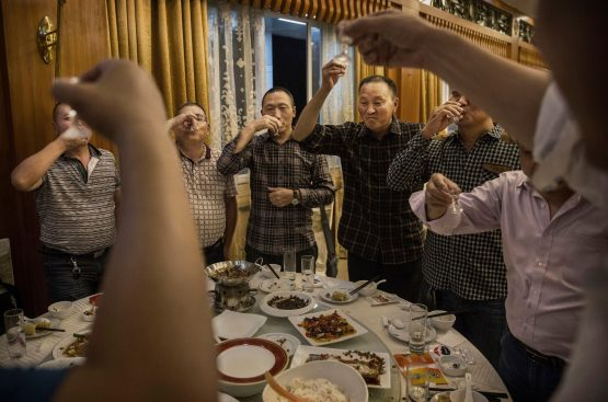 Chinese men toast each other and drink Moutai, the most famous wine called baijiu. Image: Kevin Frayer, Getty Images