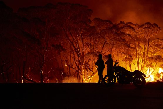 Residents look on as flames burn through bush on January 04, 2020 in Lake Tabourie, Australia. Image: Getty Images