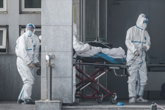Medical staff members carry a patient into the Jinyintan hospital, where patients infected by a mysterious SARS-like virus are being treated, in Wuhan in China's central Hubei province. Image: Getty Images