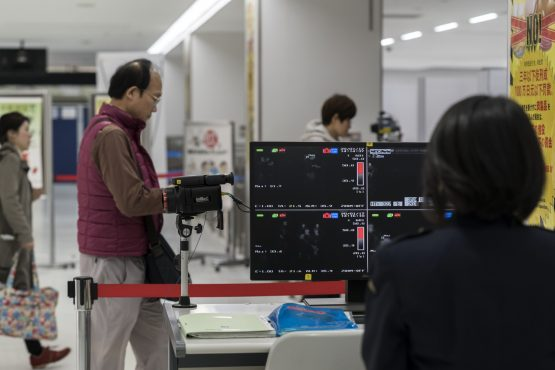 A health worker monitors a thermal scanner as passengers arrive at Narita airport on January 17, 2020 in Narita, Japan. Image: Getty Images