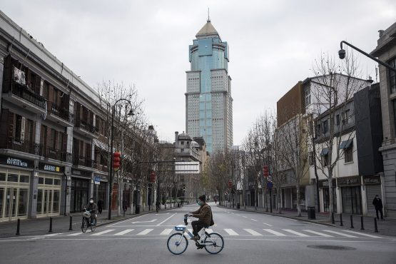 A man by bicycles past an empty street on February 8, 2020 in Wuhan, Hubei province, China. Image: Getty Images