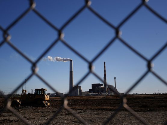 A Caterpillar Inc. bulldozer sits parked nearby as emissions rise from a smokestack at the Kentucky Utilities Co. Image: Luke Sharrett, Bloomberg