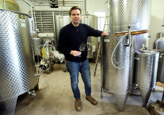 Winemaker Jens Zimmerle stands next to the steel tank containing the fermented ice wine must of the 2019 grape harvest at his vineyard in Korb near Stuttgart, Germany.