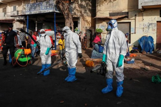 Members of local hygiene services wear protective suits and face masks as they prepare to disinfect the street and market to stop the spread of coronavirus disease in Dakar, Senegal March 22, 2020. Image: Reuters
