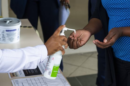 A healthcare worker pumps sanitising hand gel onto the hands of a visitor at a health screening desk outside the entrance to Netcare Pretoria East Hospital in Pretoria. Image: Waldo Swiegers/Bloomberg