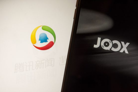The loading pages for Tencent Holdings's news , left, and music JOOX applications are displayed on Apple iPhone. Image: Anthony Kwan/Bloomberg