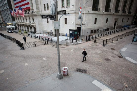 A pedestrian wearing a protective mask walks along Wall Street in front of the New York Stock Exchange in New York. Image: Michael Nagle/Bloomberg