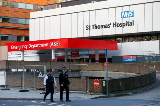 Police officers patrol outside an entrance to the emergency department at St Thomas' Hospital where UK Prime Minister Boris Johnson is being cared for in intensive care. Image: Bloomberg