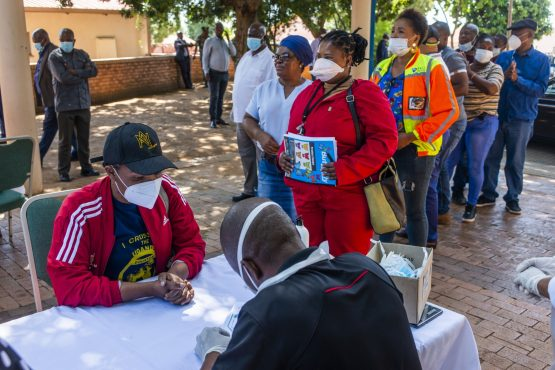 Residents wearing protective face masks queue to speak to a health worker during a health screening in Rustenburg, on April 7. Image: Bloomberg