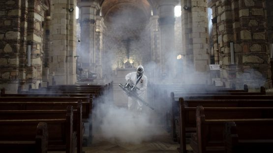 A worker wearing a protective suit disinfects a cathedral in Zipaquira, Colombia, on April 8. Image: Bloomberg