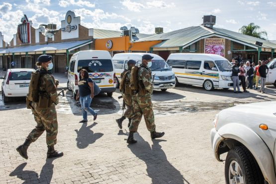 Armed soldiers from the SANDF patrol a taxi rank and adjacent shopping centre in Rustenburg. Image: Bloomberg