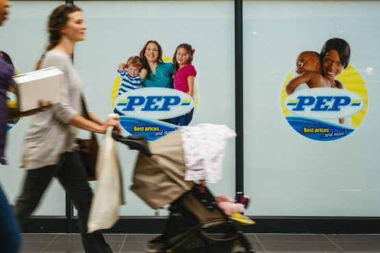 A pedestrian pushes a baby stroller past a PEP retail store, operated by Pepkor. Image: Waldo Swiegers/Bloomberg