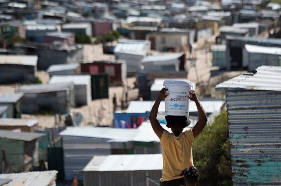 A woman carries a bucket of fresh water to an informal settlement in Khayelitsha, near Cape Town. South Africa has the widest wealth gap in the world. Image: Getty Images