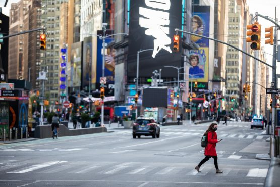 A pedestrian wearing a protective mask crosses a street in the Times Square area of New York, on Tuesday, May 12, 2020. Image: Bloomberg
