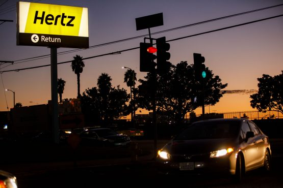 Signage is displayed at dusk outside of a Hertz Global rental location at Los Angeles International Airport in Los Angeles, California. Image: Patrick T. Fallon/Bloomberg