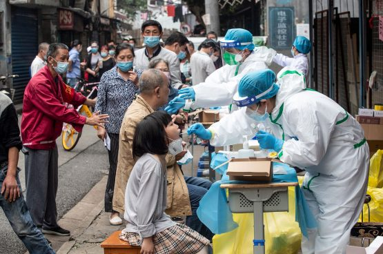 Medical workers take swab samples from residents to be tested for the Covid-19 coronavirus, in a street in Wuhan in China's central Hubei province on May 15, 2020. Images: STR/AFP/Getty Images