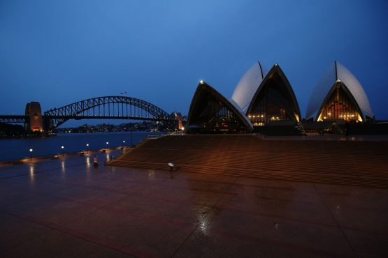 A pedestrian holding an umbrella walks along the Sydney Opera House forecourt during a partial lockdown imposed due to the coronavirus. Image: Brendon Thorne/Bloomberg