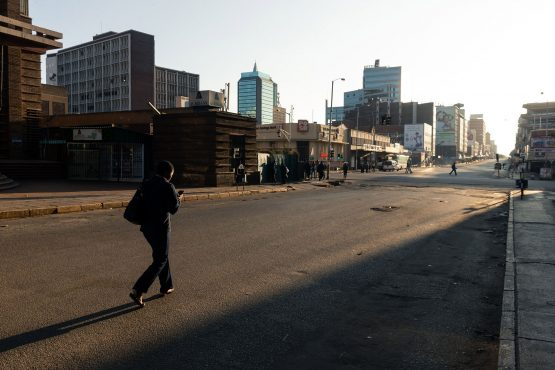A lone pedestrian makes her way in the usually bustling part of Harare central business district on March 30, 2020, which resembled a ghost town during the early morning hours of the first day of a scheduled 21-day lockdown declared by the Zimbabwe government to try and curb the further spread of the Covid-19 coronavirus. Image: Jekesai Njikizana/AFP/Getty Images