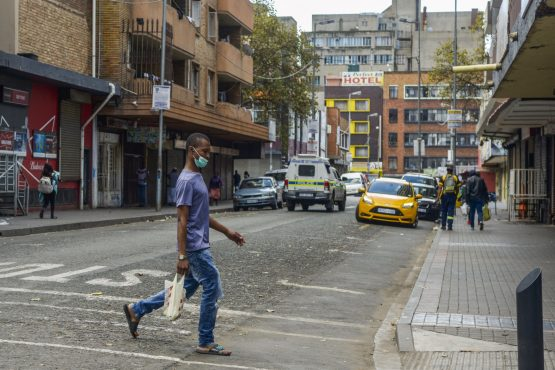 A pedestrian wearing a face mask crosses the road in the Central Business District of Johannesburg, last year. Image: Waldo Swiegers, Bloomberg
