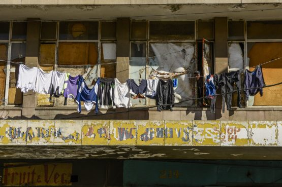 Clothing hangs on a washing line in front of windows of a dilapidated residential apartment in the CBD of Johannesburg. Image: Waldo Swiegers/Bloomberg