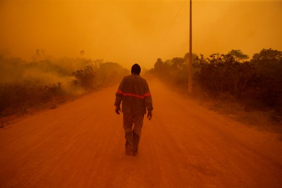 A volunteer firefighter walks along Transpantaneira road at the Pantanal wetlands region in Porto Jofre city, Mato Grosso state, Brazil, on Friday, Sept. 11, 2020. Image: Bloomberg
