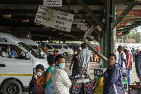Commuters wearing protective masks wait at a taxi rank in Rustenburg, April 2020. Image: Waldo Swiegers, Bloomberg