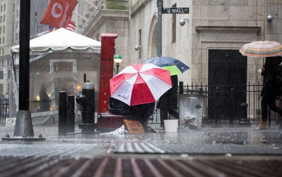 A man sits under an umbrella in the rain on Wall Street outside the New York Stock Exchange. Image: Bloomberg