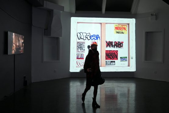 A woman walks past a projection of a NFT, or non-fungible token, high resolution short video work of art at the Superchief NFT Gallery in New York. Image: Anthony Behar, Sipa USA