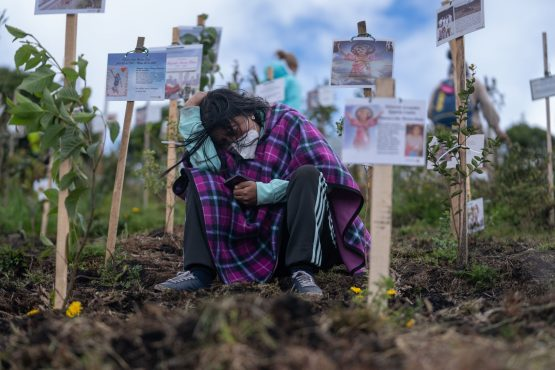 A mourner grieves over the scattered ashes of a Covid-19 victim at a nature preserve in Colombia, which has reported over 118 000 virus-related deaths. Image: Bloomberg