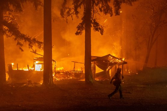 A firefighter monitors a fire as multiple structures burn in the Indian Falls neighborhood during the Dixie Fire near Crescent Mills, California, US, on Saturday, July 24, 2021. At more than 221 square miles in size, the Dixie Fire is now the largest wildfire in California. Image: Bloomberg