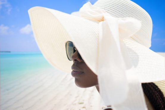 A portrait of woman wearing a summer hat and sunglasses on tropical beach. It's important now more than ever for African destinations to promote domestic tourism. Jasmin Merdan via GettyImages