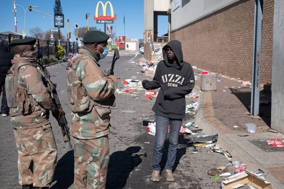 South African soldiers interrogate a pedestrian outside a mall in Soweto. Photo by Emmanuel Croset/AFP via Getty Images