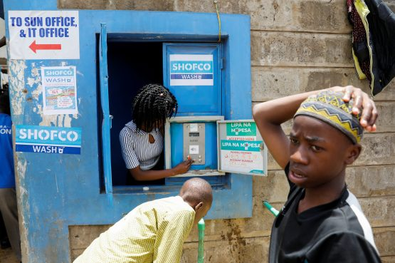 An employee of community organisation Shining Hope for Communities (SHOFCO) activates a water selling machine at a in the Kibera slum in Nairobi, Kenya, March 18, 2020. Image: Baz Ratner, Reuters
