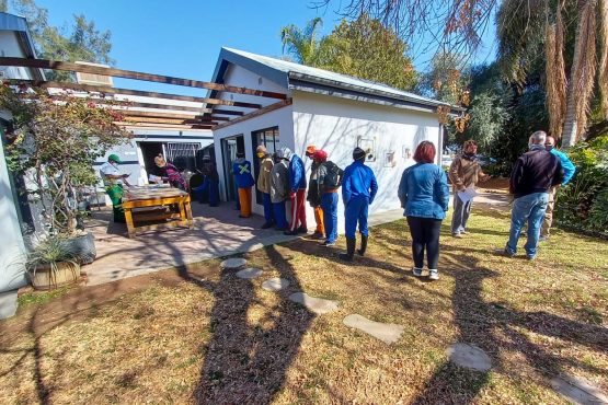 Farmworkers line up at Schalk van der Merwe's house to register for vaccination. Image: Bloomberg