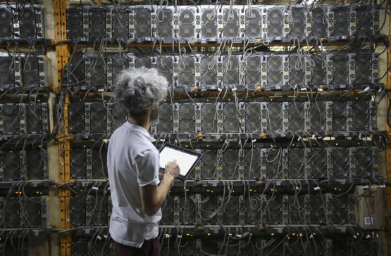 A worker inspects Bitcoin mining machines. Image: Christinne Muschi, Bloomberg