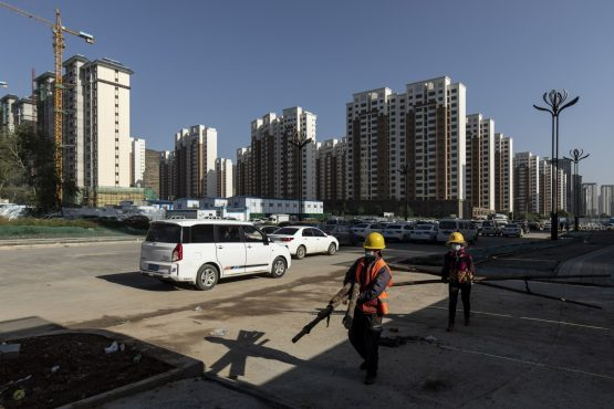 Workers carry wooden poles near apartment blocks under construction in the Nanchuan area of Xining, Qinghai province, China. Image: Qilai Shen, Bloomberg